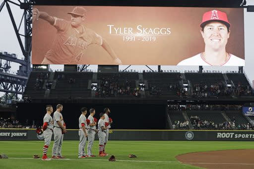 St. Louis Cardinals players stand on the field at T-Mobile Park in Seattle, Tuesday, July 2, 2019 during a moment of silence in memory of Los Angeles Angels pitcher Tyler Skaggs, prior to the Cardinals' baseball game against the Seattle Mariners. Skaggs was found unresponsive in his hotel room in Texas on Monday. (AP Photo/Ted S. Warren)