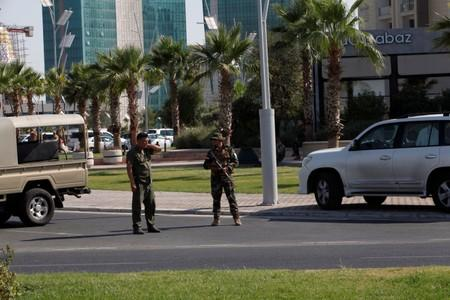 Kurdish security members stand guard near a restaurant where Turkish diplomats and Turkish consulate employee were killed in Erbil