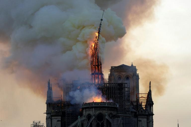 - AFP PICTURES OF THE YEAR 2019 -  The steeple and spire of the landmark Notre-Dame cathedral collapses as it is engulfed in flames in central Paris on April 15, 2019.   A huge fire swept through the roof of the famed Notre-Dame Cathedral in central Paris on April 15, 2019, sending flames and huge clouds of grey smoke billowing into the sky. The flames and smoke plumed from the spire and roof of the gothic cathedral, visited by millions of people a year. A spokesman for the cathedral told AFP that the wooden structure supporting the roof was being gutted by the blaze