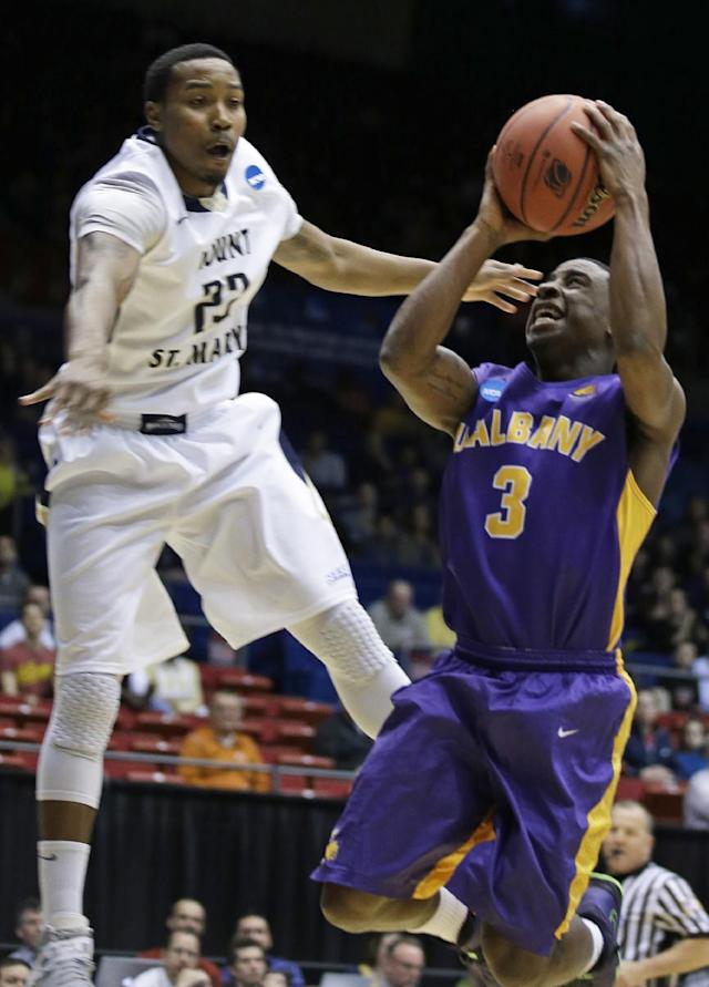 Albany guard DJ Evans (3) drives against Mount St. Mary's guard Julian Norfleet in the first half of a first-round game of the NCAA college basketball tournament, Tuesday, March 18, 2014, in Dayton, Ohio. (AP Photo/Al Behrman)