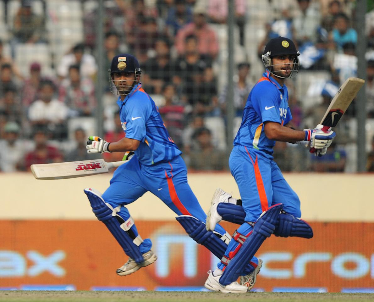 Indian batsman Gautam Gambhir (L) and his teammate Virat Kholi (R) run between the wickets during the one day international (ODI) Asia Cup cricket match between India and Sri Lanka at The Sher-e-Bangla National Cricket Stadium in Dhaka on March 13, 2012. AFP PHOTO/Munir uz ZAMAN (Photo credit should read MUNIR UZ ZAMAN/AFP/Getty Images)