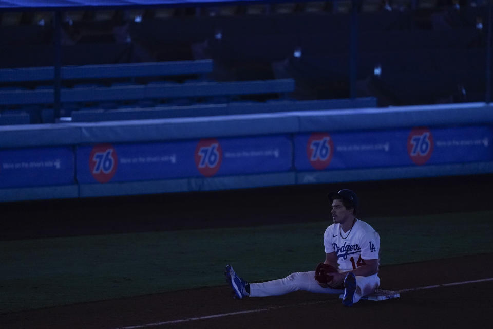 Los Angeles Dodgers left fielder Enrique Hernandez sits on third base during a power outage that stopped a baseball game against the Los Angeles Angels in the seventh inning Saturday, Sept. 26, 2020, in Los Angeles. (AP Photo/Ashley Landis)