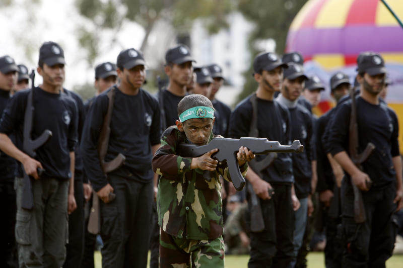 A Palestinian boy holds a rifle-shaped wooden stick during a graduation ceremony for the first group of school children's military training organized by Hamas education ministry in Gaza City, Thursday, Jan. 24, 2013. (More than 3,000 Palestinian teenagers on Thursday graduated from the ruling Hamas militant group's first high school military training program in the Gaza Strip, displaying mock weapons, crawling commando-style on the ground and taking up fighting positions for thousands of cheering supporters. AP Photo/Adel Hana)