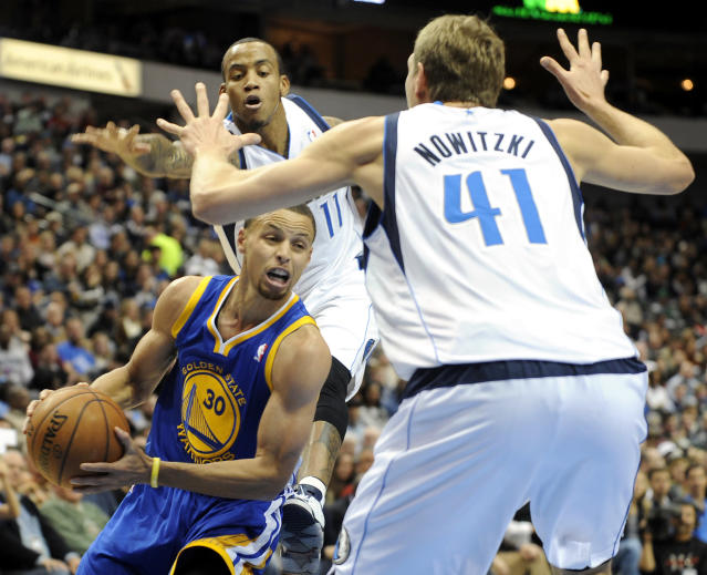 Golden State Warriors point guard Stephen Curry (30) drives between Dallas Mavericks shooting guard Monta Ellis (11) and power forward Dirk Nowitzki (41) in the first half during an NBA basketball game on Wednesday, Nov. 27, 2013, in Dallas. (AP Photo/Matt Strasen)