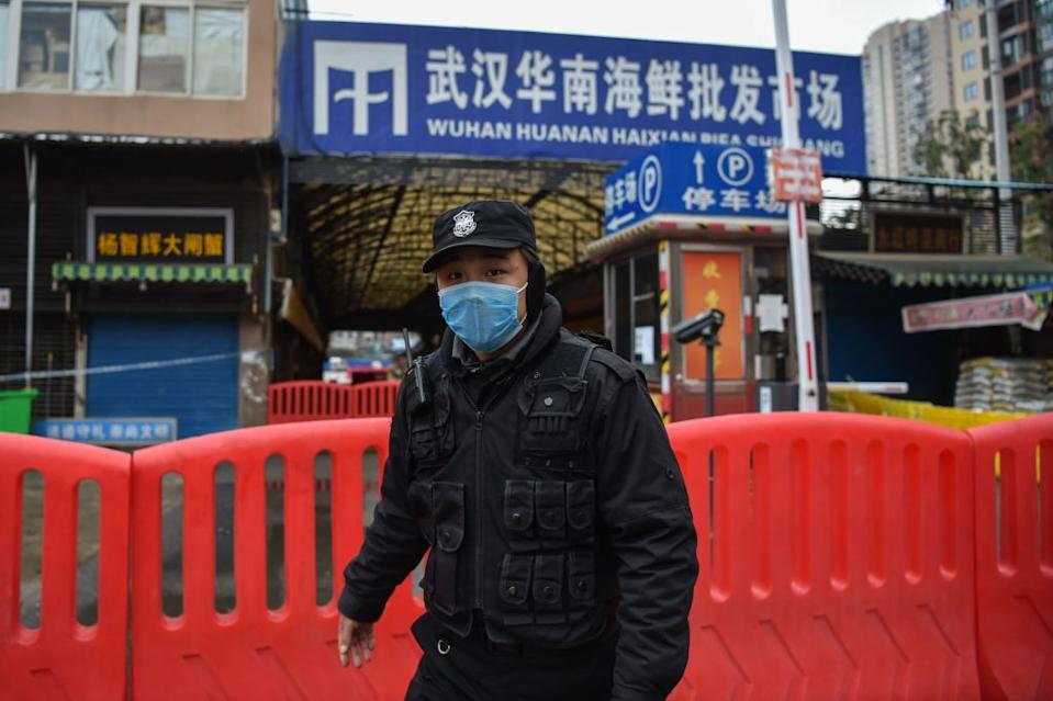 A police officer stands guard outside of Huanan Seafood Wholesale market where the coronavirus is believed to have originated. Source: Getty