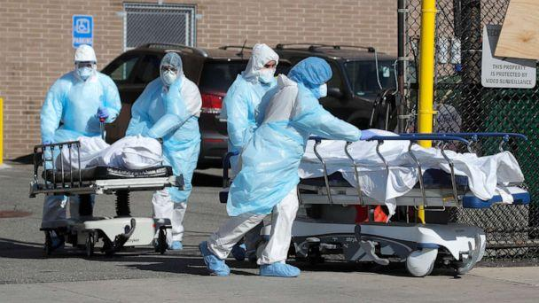 PHOTO: Healthcare workers wheel the bodies of deceased people outside the Wyckoff Heights Medical Center during the outbreak of the coronavirus disease (COVID-19) in Brooklyn, New York, April 6, 2020. (Brendan Mcdermid/Reuters)