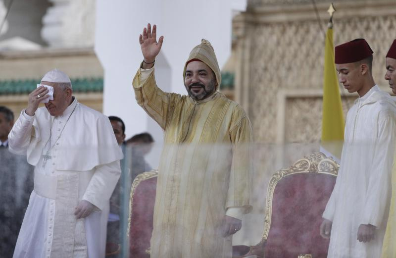 Moroccan King Mohammed VI waves as Pope Francis wipes his forehead, in Rabat, Morocco, Saturday, March 30, 2019. Francis's weekend trip to Morocco aims to highlight the North African nation's tradition of Christian-Muslim ties while also letting him show solidarity with migrants at Europe's door and tend to a tiny Catholic flock on the peripheries. (AP Photo/Gregorio Borgia)