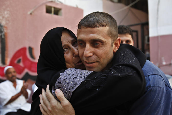 Nehad Jondiya, a Palestinian released after 24 years in an Israeli jail, hugs his sister, Um rami, at his family's house in Gaza City on Wednesday, Aug. 14, 2013. Israelis and Palestinians were to hold their first formal peace talks on home turf in the Middle East in nearly five years Wednesday, hours after Israel released 26 long-held Palestinian prisoners who were given a boisterous homecoming by cheering crowds. (AP Photo/Adel Hana)
