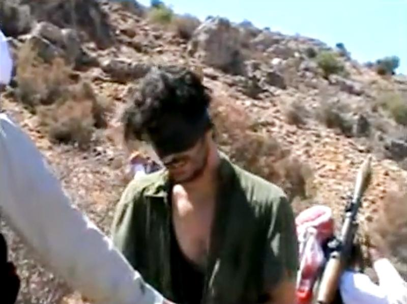 In this image taken from undated video posted to YouTube, American freelance journalist Austin Tice, who had been reporting for American news organizations in Syria until his disappearance in August 2012, prays in Arabic and English while blindfolded in the presence of gunmen. The Associated Press could not independently confirm the origin or the content of the clip, but the Tice family released a statement to several media outlets confirming it was their son in the video. Although the video footage shows a group of captors dressed and behaving like Islamic extremists, the clip lacks the customary form of jihadist videos. Previous reports have indicated that Tice is in Syrian government custody. (AP Photo)