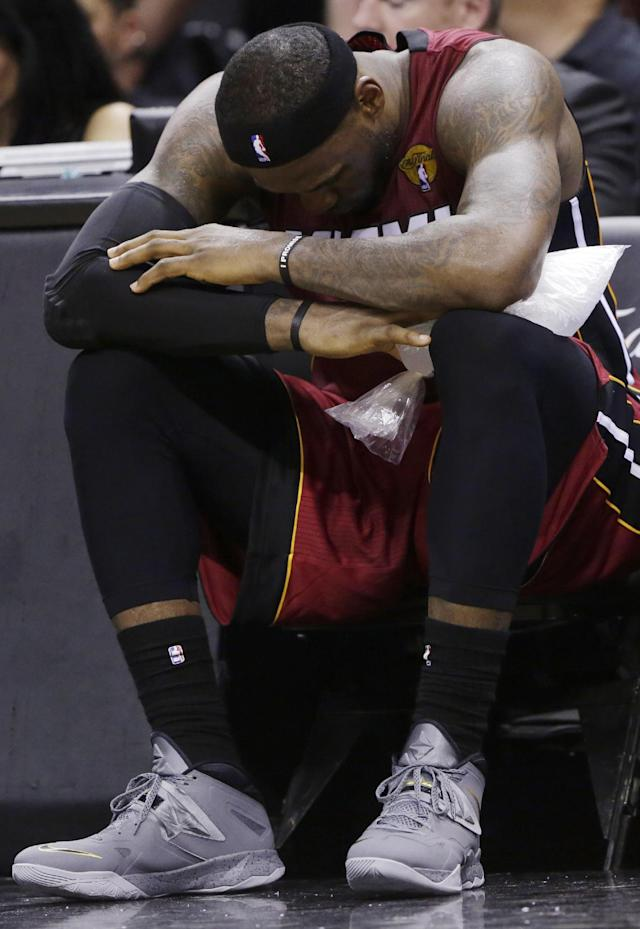 Miami Heat forward LeBron James (6) sits with ice on his leg after injuring himself against the San Antonio Spurs during the second half in Game 1 of the NBA basketball finals on Thursday, June 5, 2014 in San Antonio. (AP Photo/Eric Gay)