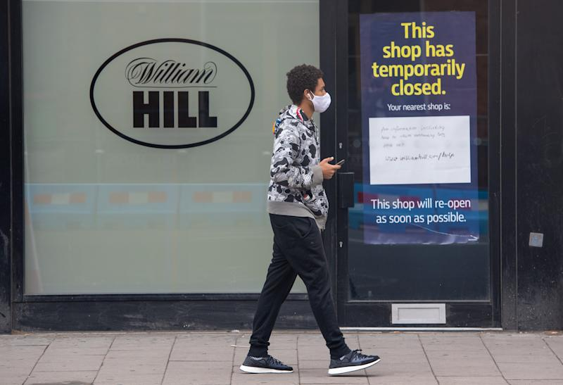 A man passes a closed branch of bookmakers William Hill in Waterloo, London, following the introduction of measures to bring England out of lockdown. (Photo by Dominic Lipinski/PA Images via Getty Images)
