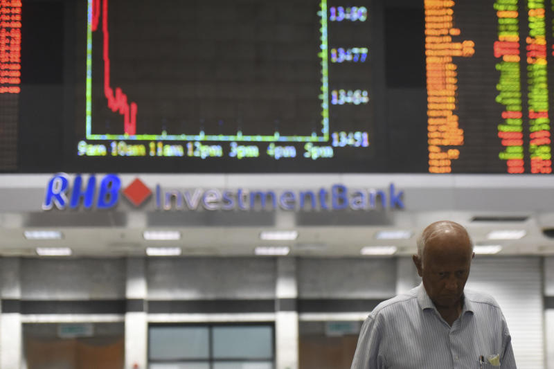An investor walks in front of private stock trading boards at a private stock market gallery in Kuala Lumpur, Malaysia, Monday, Oct. 22, 2018. Asian markets were mixed on Monday although Chinese benchmarks rallied after officials put a positive spin on the country's slowing economy. (AP Photo/Yam G-Jun)