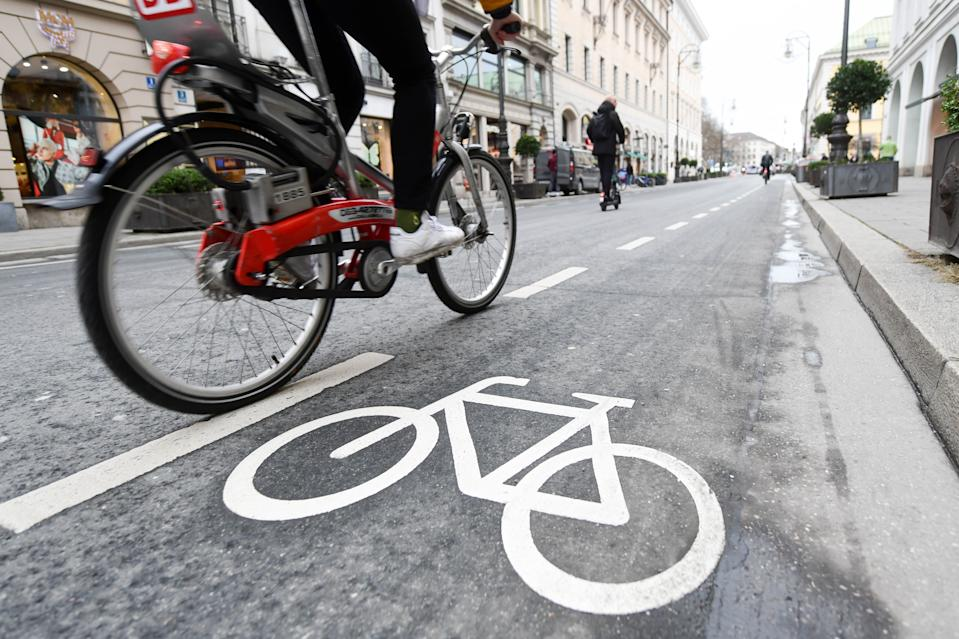 """08 January 2020, Bavaria, Munich: A cyclist and a scooter driver pass the markings for a cycle path on the Brienner Straße. Until recently the Brienner Straße was passable for cars in both directions, there was no cycle path. In the future, there will be less space for cars in Munich's city centre. Cyclists and pedestrians should benefit. First measures have already been implemented.     (to dpa """"Operation at the heart: Munich gets tips for car-free old town """" from 08.01.2020) Photo: Tobias Hase/dpa (Photo by Tobias Hase/picture alliance via Getty Images)"""