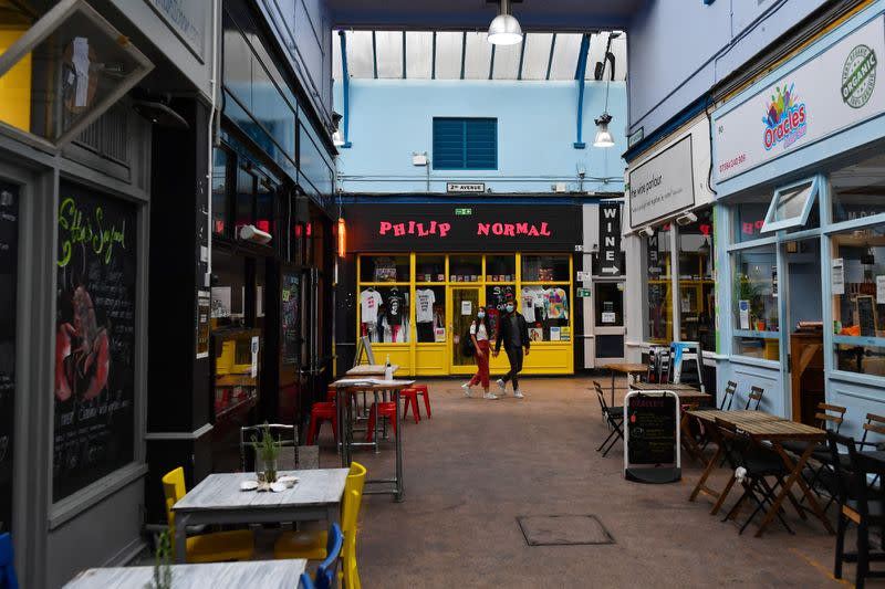 A couple walk past empty restaurants during a quiet night at Brixton Village in London