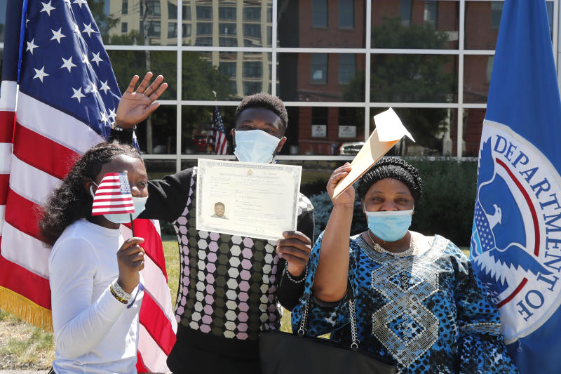 RETRANSMISSION TO CORRECT NAME TO ALBERT BARAKA - Albert Baraka, middle, celebrates his new citizenship with his sister, Delice, left, and his mother, Florence after ceremonies, Thursday, June 4, 2020, in Lawrence, Mass. The federal agency charged with overseeing legal immigration and citizenship is resuming services in many cities across the country after being shuttered for more than two months because of the coronavirus pandemic. (AP Photo/Elise Amendola)