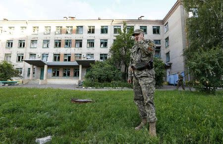 A pro-Russia separatist patrols near a maternity ward in the eastern Ukrainian city of Slaviansk June 16, 2014. REUTERS/Shamil Zhumatov