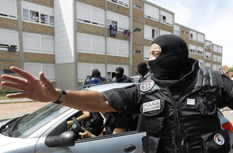 A French special Police forces officer gestures as Police escorts a woman from a residential building during a raid in Saint-Priest