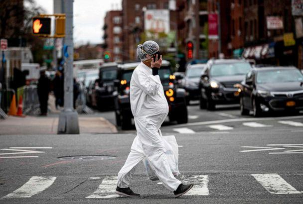 PHOTO: A pregnant woman wearing a protective suit and a mask crosses the streets in the Elmhurst neighborhood of Queens, April 27, 2020 in New York City. (Johannes Eisele/AFP via Getty Images)