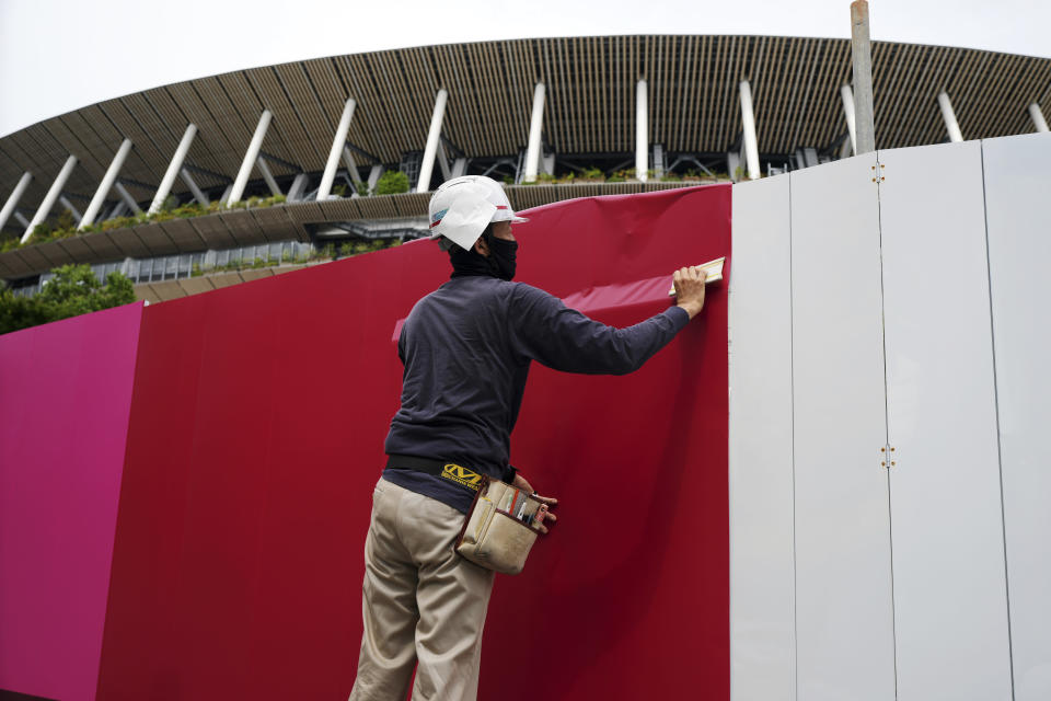 Workers place the overlay on the wall of the National Stadium, where opening ceremony and many other events are scheduled for the postponed Tokyo 2020 Olympics, Wednesday, June 2, 2021, in Tokyo. (AP Photo/Eugene Hoshiko)