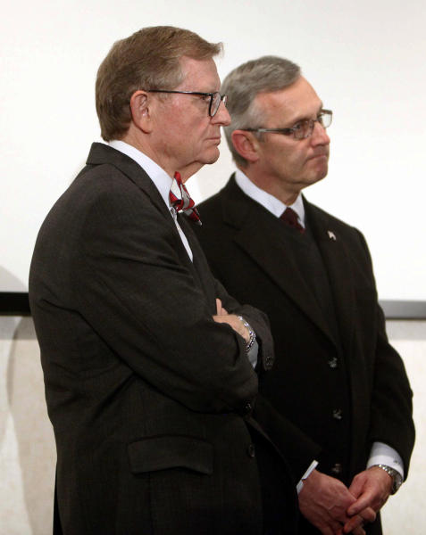 """FILE - In this March 8, 2011 file photo, Ohio State football coach Jim Tressel, right, and university President E. Gordon Gee listen as athletic director Gene Smith speaks during a news conference in Columbus, Ohio. As the country absorbs the independent report released Thursday, July 12, 2012, on the Penn State sex abuse scandal, some see it as more than an indictment of one school. They see it as underscoring how major-college sports, football in particular, have run amok. When Gee heard Tressel concede he had reason to believe several star players were taking money and free tattoos from a suspected drug dealer and yet he had told no one, Gee was asked if he had considered firing Tressel. """"Let me just be very clear,"""" Gee said with a grin, """"I'm just hopeful the coach doesn't dismiss me."""" The joke fell flat, but echoed around the country. It confirmed what many already believed about the balance of power in college sports today: some football teams run universities, not the other way around. (AP Photo/Terry Gilliam, File)"""