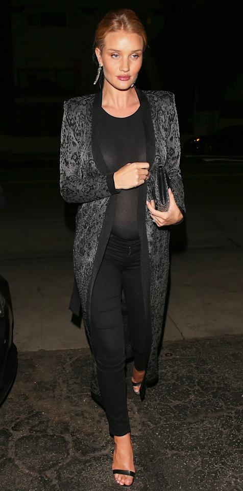 """<p>Huntington-Whiteley stepped out for dinner with Jason Statham in a sheer black top that showed off her growing belly. She paired the look with a silk duster, black jeans, and strappy black heels (shop a similar style from <a rel=""""nofollow"""" href=""""https://click.linksynergy.com/fs-bin/click?id=93xLBvPhAeE&subid=0&offerid=390098.1&type=10&tmpid=8157&RD_PARM1=http%253A%252F%252Fshop.nordstrom.com%252Fs%252Fsam-edelman-yaro-ankle-strap-sandal-women%252F4447280%253Forigin%253Dcategory-personalizedsort%2526fashioncolor%253DBLACK%252520NAPPA%252520LEATHER&u1=ISNEWSRosieHWShoes3.15OB"""">Nordstrom</a>).</p>"""