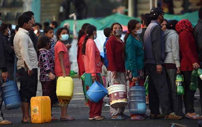 Nepalese people stand in line for water on April 28, 2015 at a camp set up in quake-ravaged Kathmandu (AFP Photo/Prakash Singh)