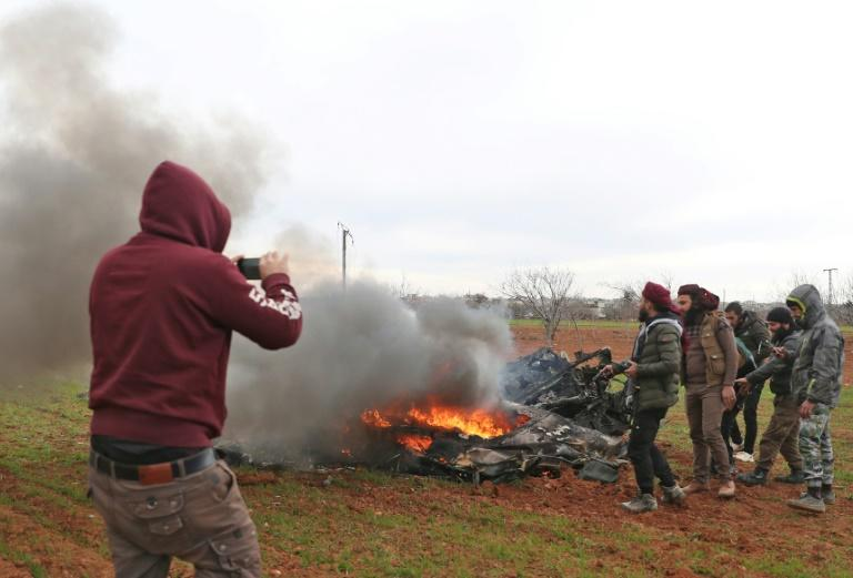 Syrian rebel fighters gather around the burning remains of a downed military helicopter (AFP Photo/Omar HAJ KADOUR)