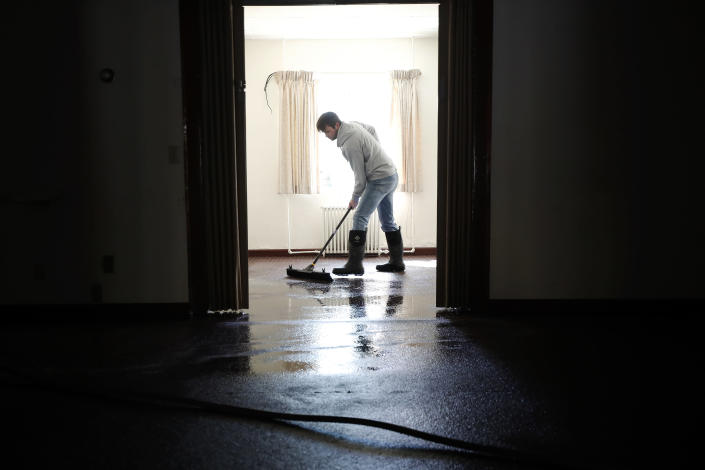 Brandon Lynch, of Beattyville, Ky., works to clear water inside of Newnam Funeral Home after heavy rains caused the Kentucky River to flood most of downtown Beattyville, Ky., Tuesday, March 2, 2021. (Alex Slitz/Lexington Herald-Leader via AP)