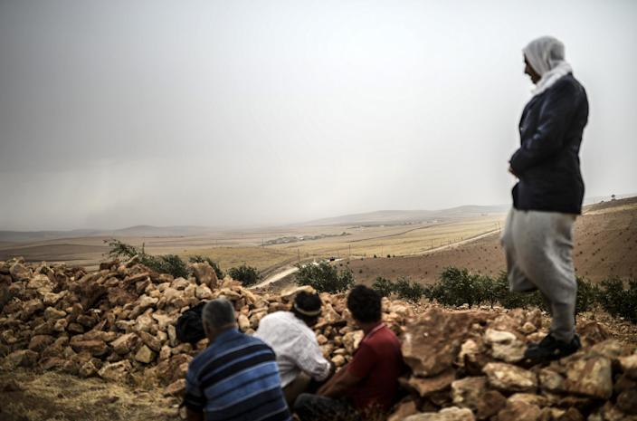 Syrian Kurds watch clashes between jihadists of the Islamic State and Kurdish fighters, at Swedi village some 10 km west of Suruc in Sanliurfa province, Turkey on September 24, 2014 (AFP Photo/Bulent Kilic)