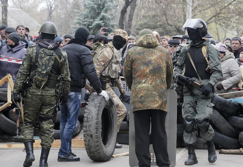 Armed pro-Russian activists occupy the police station and build a barricade as people watch on, in the eastern Ukrainian town of Slovyansk on Saturday, April 12, 2014. Pro-Moscow protesters have seized a number of government buildings in the east over the past week, undermining the authority of the interim government in the capital, Kiev. (AP Photo/Efrem Lukatsky)