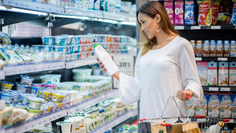 Asian woman grocery shopping at the market and holding a bottle of milk - dairy products concepts.