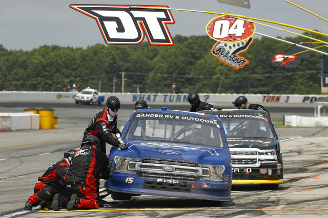 Crew members service the truck of Tanner Gray, left, in the pits during the NASCAR Truck Series auto race at Pocono Raceway, Sunday, June 28, 2020, in Long Pond, Pa. (AP Photo/Matt Slocum)