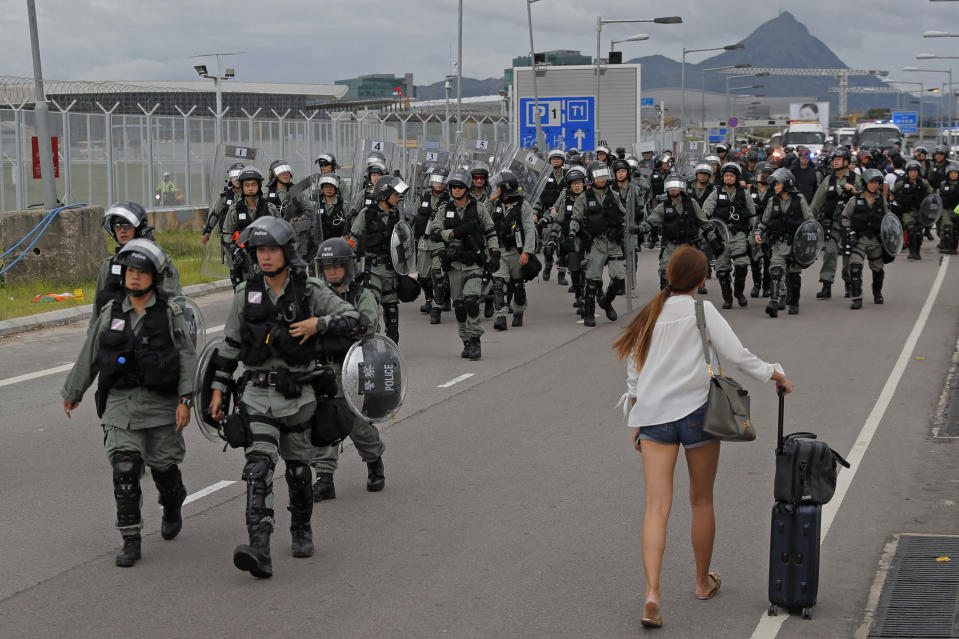 A passenger walks pass riot polices as protestors blocked a road outside the airport in Hong Kong, Sunday, Sept .1, 2019. Train service to Hong Kong's airport was suspended Sunday as pro-democracy demonstrators gathered there, while protesters outside the British Consulate called on London to grant citizenship to people born in the former colony before its return to China. (AP Photo/Kin Cheung)