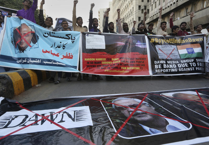 In this Tuesday, Dec. 3, 2019, photo, angry Islamists chant slogans during a demonstration against an independent Pakistani newspaper Dawn, at outside the Press Club in Karachi, Pakistan. Dozens of angry Islamists swarmed the building of an independent Pakistani newspaper in the capital, Islamabad, blocking its entrance for several hours, threatening the staff and demanding its editor be hanged, the newspaper reported Wednesday. (AP Photo/Fareed Khan)