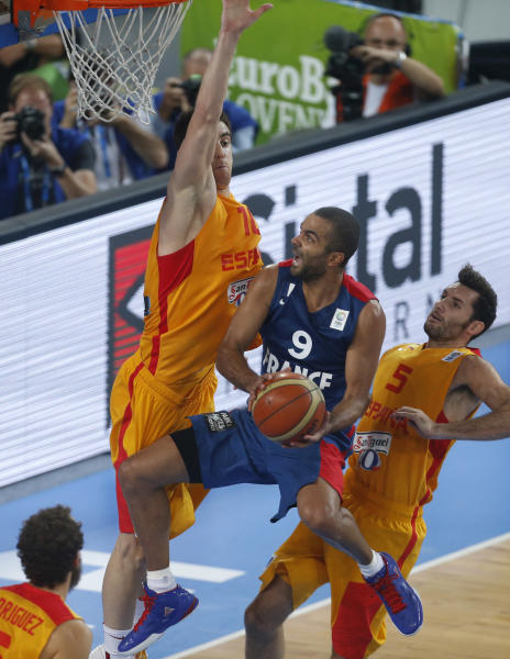 France's Tony Parker, center, challenges for the ball with Spain's Victor Claver, left and Spain's Rudy Fernandez, right, during their EuroBasket European Basketball Championship semifinal match in Ljubljana, Slovenia, Friday, Sept. 20, 2013. (AP Photo/Darko Bandic)