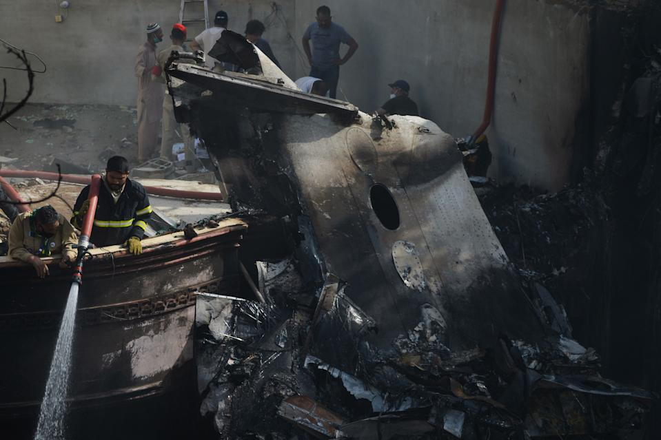 A firefighter sprays water on the wreckage of a Pakistan International Airlines aircraft after it crashed in a residential area in Karachi on May 22, 2020. - A Pakistani plane with nearly 100 people on board crashed into a residential area in the southern city of Karachi on May 22, killing several people on the ground. (Photo by Rizwan TABASSUM / AFP) (Photo by RIZWAN TABASSUM/AFP via Getty Images)