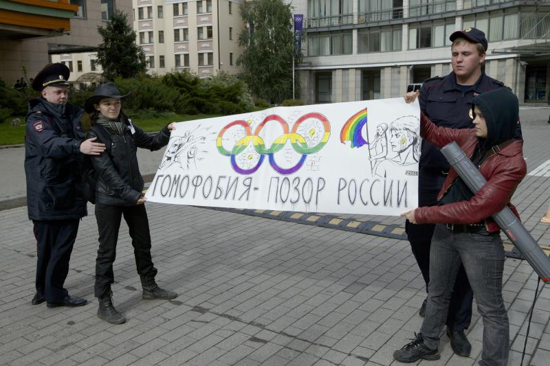 "FILE - In this Wednesday, Sept. 25, 2013 file photo, police officers detain two gay rights activists holding a poster reading ""Homophobia is Russia's Disgrace"" during a protest outside the Sochi 2014 Winter Olympic Games organizing committee office, in downtown Moscow, Russia. Despite months of protests, Russia's law against ""gay propaganda"" remains in place, and no major boycott of the Russian-hosted Winter Olympics seems likely. (AP Photo/Ivan Sekretarev, File)"