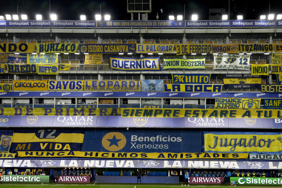Banners placed by fans fill the empty stands of Bombonera stadium during a soccer match between Boca Juniors and Racing Club in Buenos Aires, Argentina, Monday, Aug. 30, 2021. Four hours before the match, soccer fans are allowed to enter and hang banners but must remove them after the match, amid COVID-19 restrictions that ban fans from attending games. (AP Photo/Natacha Pisarenko)