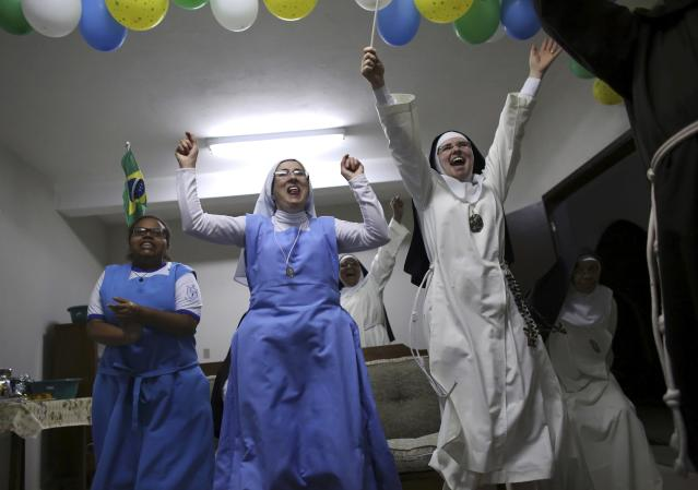 Nuns from the enclosed monastery of Imaculada Conceicao celebrate Brazil's victory as they watch on television at the end of the 2014 World Cup quarter-final soccer match between Brazil and Colombia in Piratininga, in Sao Paulo state, July 4, 2014. REUTERS/Nacho Doce (BRAZIL - Tags: SPORT SOCCER WORLD CUP SOCIETY RELIGION)