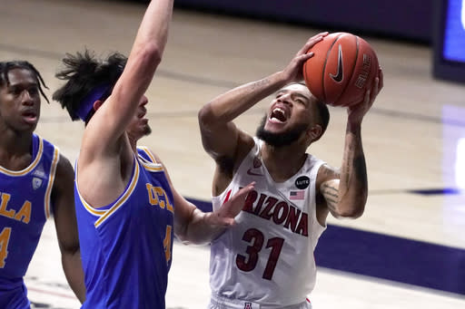 Arizona guard Terrell Brown Jr. (31) shoots in front of UCLA guard Jaime Jaquez Jr. during the first half of an NCAA college basketball game Saturday, Jan. 9, 2021, in Tucson, Ariz. (AP Photo/Rick Scuteri)
