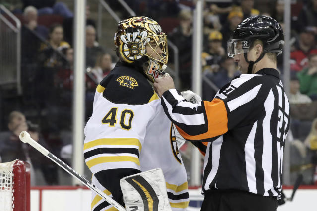 Referee Eric Furlatt (27) adjusts the mask of Boston Bruins goaltender Tuukka Rask, of Finland, during the second period of the team's NHL hockey game against the New Jersey Devils, Thursday, March 21, 2019, in Newark, N.J. (AP Photo/Julio Cortez)