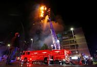 The corporate building of the multinational energy company ENEL, is seen on fire during a protest against the increase in the subway ticket prices in Santiago