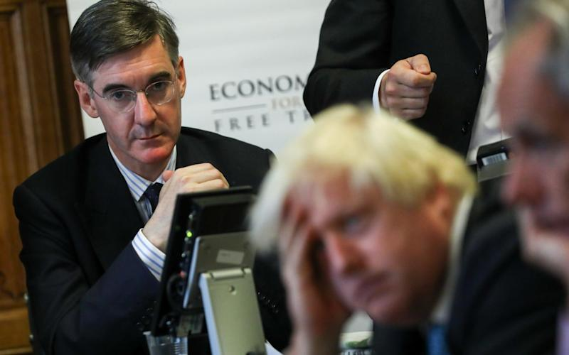 Jacob Rees-Mogg and Boris Johnson listening to their fellow Brexiteers - Bloomberg