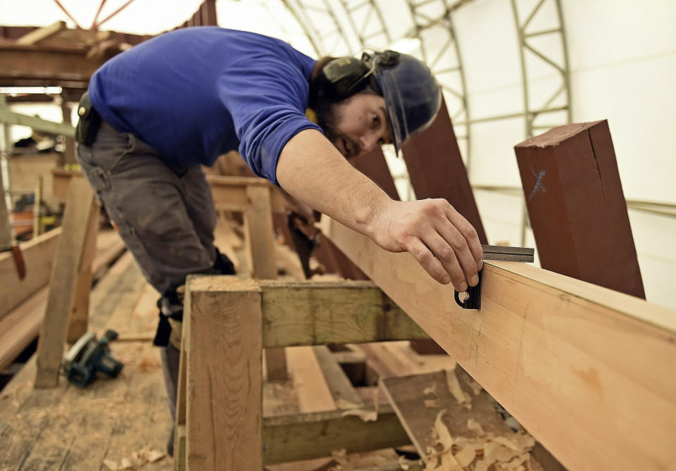FILE- In this Feb. 21, 2019 file photo, shipwright Mike Brittan checks his work as he planes a deck plank for the main deck of the Mayflower II at the Mystic Seaport in Mystic, Conn. The Mayflower II is set to leave Mystic Seaport on Monday, July 20, 2020, for a sea trials in New London, Conn., before sailing up the coast and arriving at Plimoth Plantation in Massachusetts during the second week of August 2020. (Sean D. Elliot/The Day via AP, File)