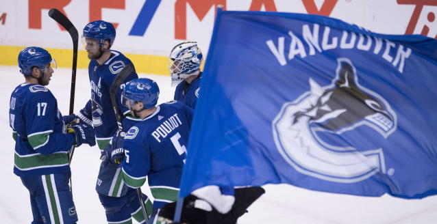 Vancouver Canucks goaltender Jacob Markstrom, right, and teammates celebrate the team's win over the St. Louis Blues in an NHL hockey game Thursday, Dec. 20, 2018, in Vancouver, British Columbia. (Jonathan Hayward/The Canadian Press via AP)