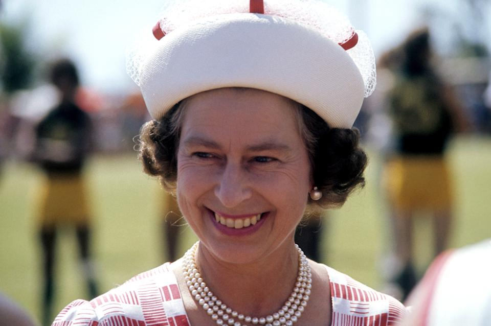 Queen Elizabeth II wearing a white hat and pearl necklace and earrings in Darwin, where she attended a Northern Territory Football League match between St Marys and Waratahs during her silver jubilee tour of Australia on 25 March 1977