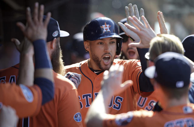 Houston Astros' George Springer is congratulated by teammates after hitting a solo home run off Cleveland Indians starting pitcher Mike Clevinger in the fifth inning during Game 3 of baseball's American League Division Series, Monday, Oct. 8, 2018, in Cleveland. (AP Photo/David Dermer)