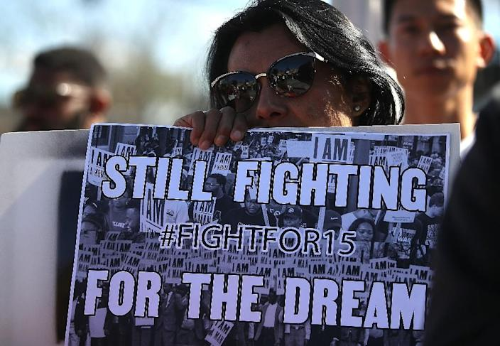 """A woman holds a sign referencing Martin Luther King Jr's """"I Have a Dream"""" speech at a protest by fast food workers (AFP Photo/JUSTIN SULLIVAN)"""