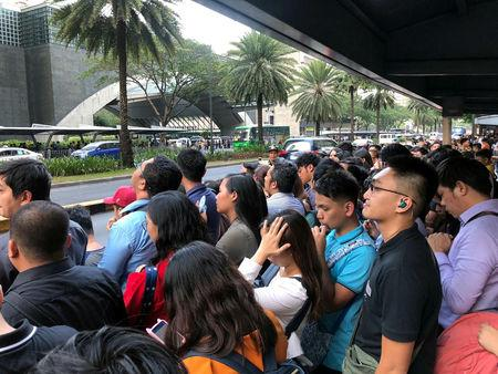 Employees wait outside after being evacuated from the office building after an earthquake in Makati City, Philippines, April 22, 2019. REUTERS/Martin Petty
