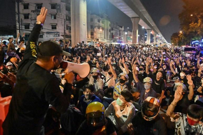 A protester uses a loudspeaker to address the crowd at Kaset intersection in Bangkok